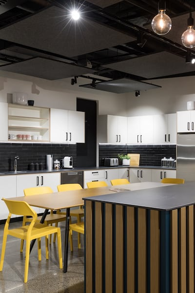 Glassons head office kitchen – white cabinets, yellow chairs